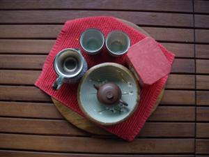 small teapot, jug, strainer and cups for making oolong tea